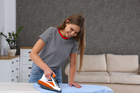 Young woman ironing clothes on board at home. Space for text