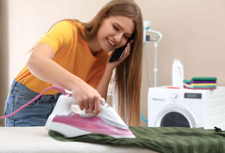 Happy woman talking on phone while ironing clothes in bathroom. Space for text Фото со стока