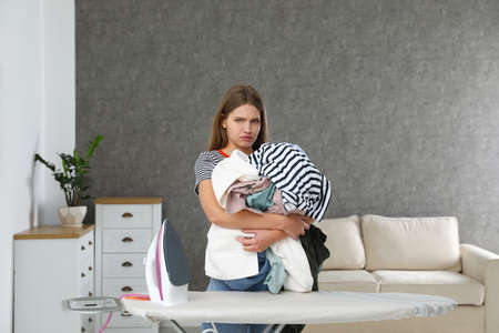 Emotional woman holding heap of clothes near ironing board at home