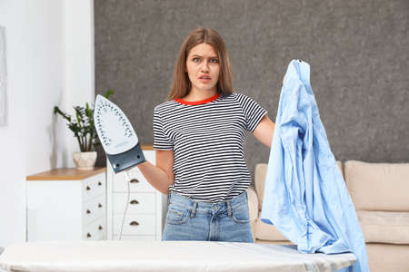 Emotional woman with iron and shirt at home