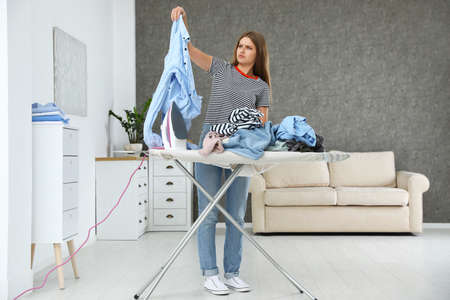Emotional woman near board with iron and pile of clothes at home