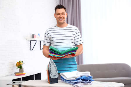 Man with folded clothes near ironing board at home Banco de Imagens - 124988505