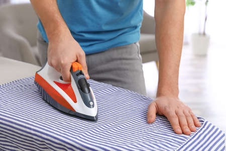 Man ironing shirt on board at home, closeup