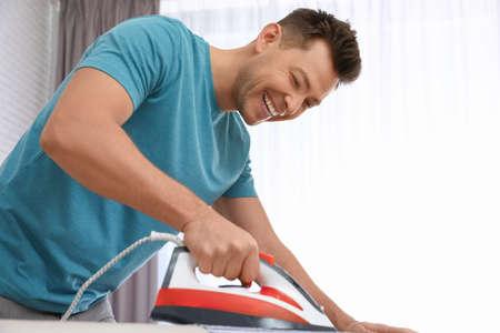 Man ironing shirt on board at home