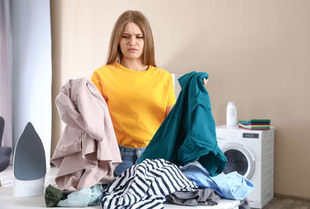 Emotional woman near board with iron and pile of clothes in bathroom