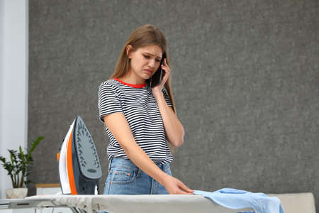 Emotional woman talking on phone while ironing clothes at home. Space for text
