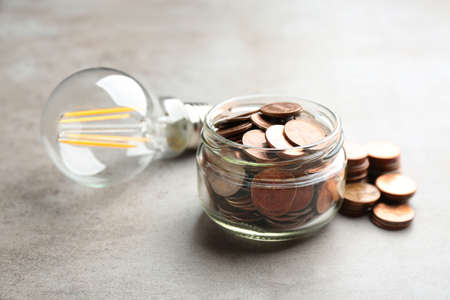 Glass jar, coins and light bulb on grey background