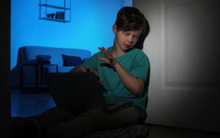 Frightened little child with laptop on floor in dark room. Danger of internet Фото со стока