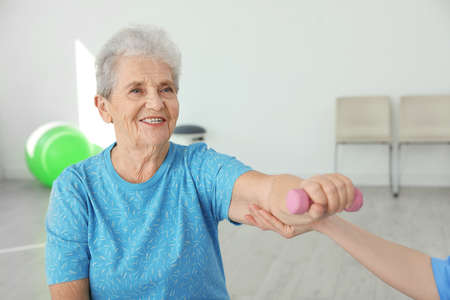 Professional physiotherapist working with elderly patient in rehabilitation center Stock Photo