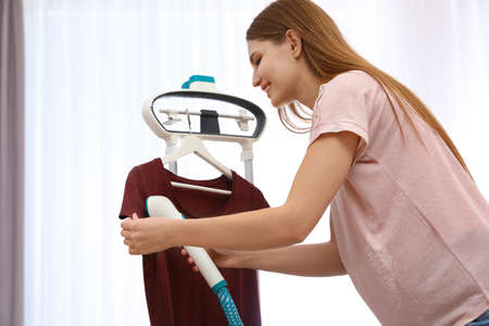 Young woman steaming her clothes on rack at home