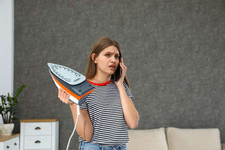 Emotional woman talking on phone while ironing clothes at home