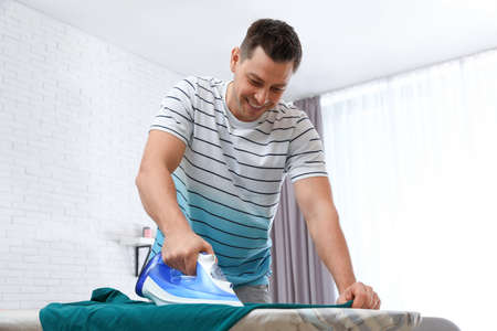 Man ironing clothes on board at home