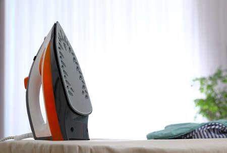 Plancha eléctrica moderna y ropa a bordo en interiores. Espacio para texto