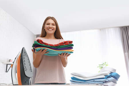 Young woman with folded clothes near ironing board at home. Space for text