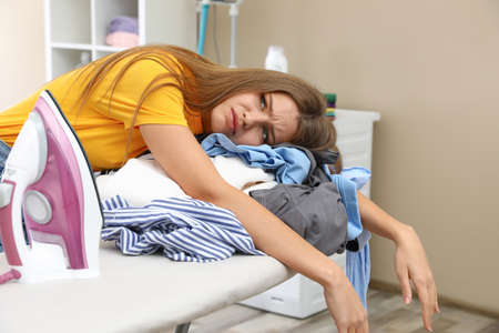 Tired woman leaning on ironing board with clothes at home Banco de Imagens - 124988494