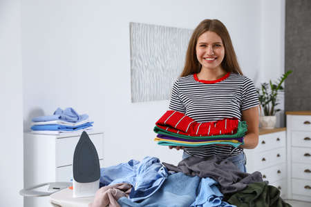 Young woman with folded clothes near ironing board at home Banco de Imagens - 124988495