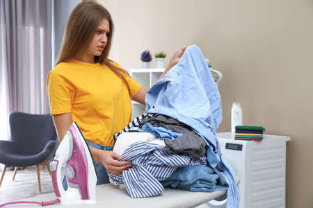 Emotional woman near board with iron and pile of clothes at home Banco de Imagens - 124988545