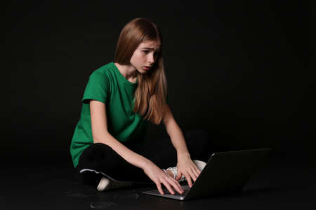Shocked teenage girl with laptop on black background. Danger of internet