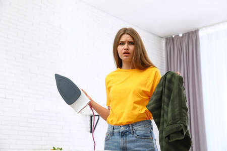 Emotional woman with iron and clothes at home