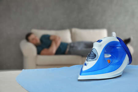 Modern iron and sleeping man in room. Space for text