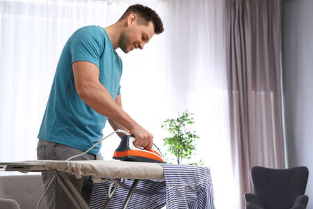 Man ironing shirt on board at home. Space for text