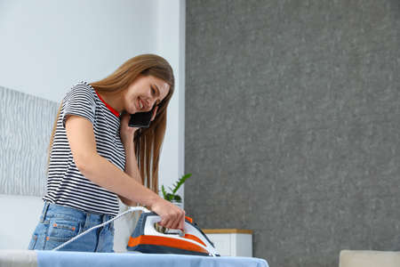 Happy woman talking on phone while ironing clothes at home. Space for text Banco de Imagens