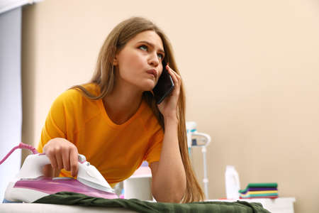 Thoughtful woman talking on phone while ironing clothes at home. Space for text