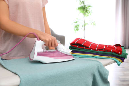 Young woman ironing clothes on board at home, closeup Archivio Fotografico