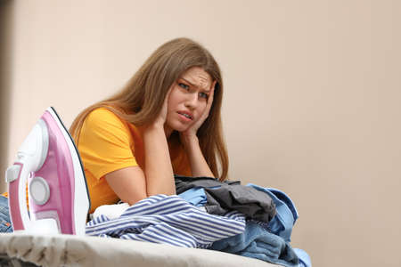 Emotional woman leaning on board with iron and pile of clothes at home. Space for text