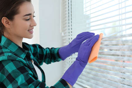Young woman wiping window blinds with rag indoors. Before and after cleaning