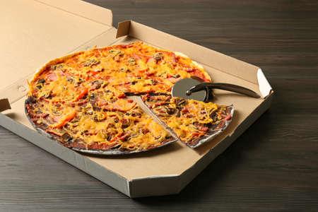 Boîte de pizza noire et blanche avec couteau sur table en bois