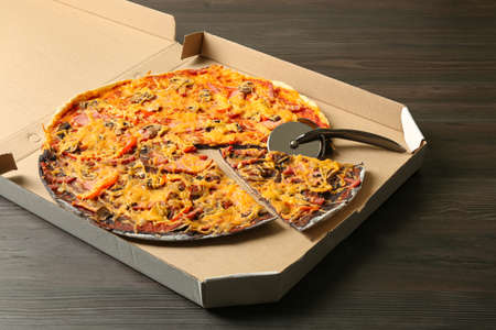 Box of black and white pizza with knife on wooden table