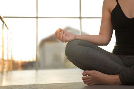 Woman practicing yoga on floor against window, closeup. Space for text Stock Photo