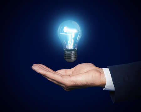 Businessman holding lamp bulb against dark background, closeup Stock Photo