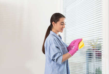 Young woman wiping window blinds with rag indoors. Before and after cleaning Stock Photo