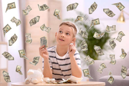 Little boy with broken piggy bank and money at home Фото со стока