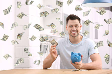 Happy man with piggy bank and money at home Imagens