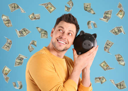 Happy man with piggy bank and flying money on color background