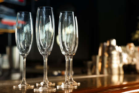 Empty clean champagne glasses on counter in bar. Space for text Reklamní fotografie
