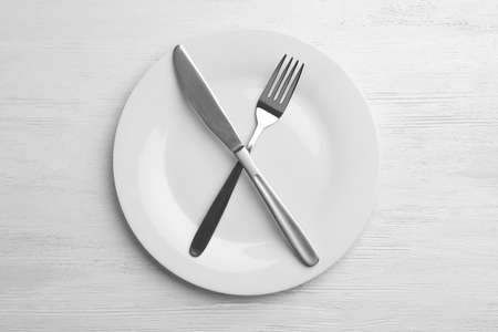 Empty plate with cutlery on white wooden background, flat lay
