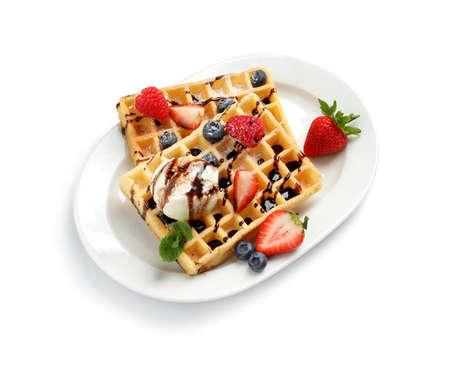 Assiette avec de délicieuses gaufres, baies et glaces sur fond blanc