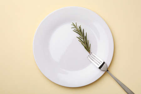 Plate with rosemary and fork on color background, flat lay Stock Photo