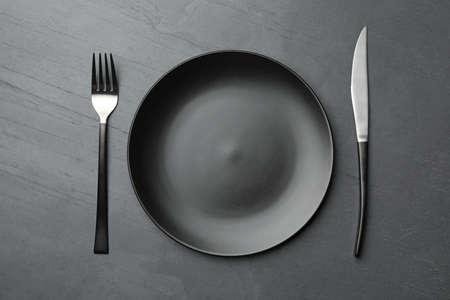 Stijlvol keramisch bord en bestek op donkere achtergrond, plat gelegd