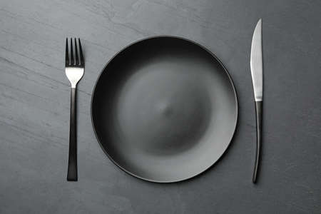 Stylish ceramic plate and cutlery on dark background, flat lay
