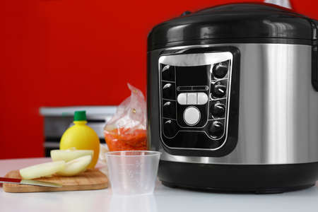 New modern multi cooker and products on table in kitchen