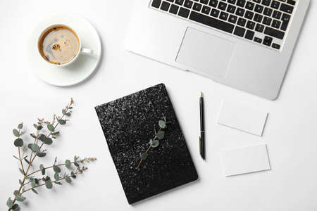 Flat lay composition with glittering notebook and laptop on white background