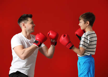 Dad and his son with boxing gloves on color background Фото со стока