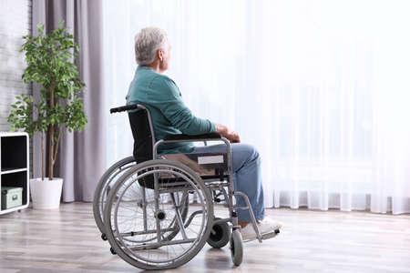 Hombre mayor sentado en silla de ruedas cerca de la ventana en casa