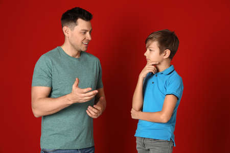 Dad talking with his son on color background