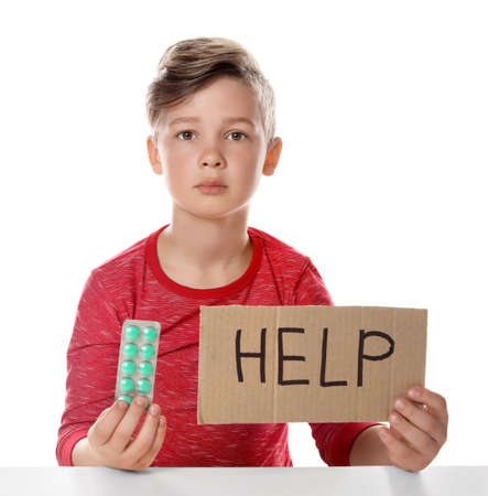 Little child with pills and word Help written on cardboard against white background. Danger of medicament intoxication